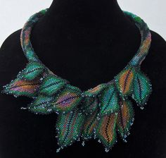 """From Thanksgiving to the end of January I toiled away. First, I covered a length of drapery cord with peyote stitch, simply letting the pattern """"happen"""". Then I individually stitched each leaf, add..."""