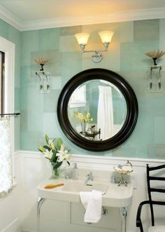 This bath is a study in contrasts. White trim, fabrics, and fixtures stand out against a wall palette of cool blues and tidewater greens painted in a mosaic design. The room's soft color palette suggests hues of the nearby ocean. Silver accents shimmer. Mahogany mirror & wood chair serve to anchor the cool tones.