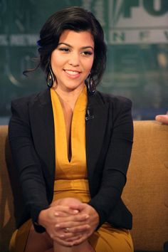 Kourtney Kardashian paired her tailored blazer and mustard cocktail dress with black tear drop hoop earrings trimmed in gold.