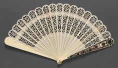 1830-1855, Russia - Brisé fan - Carved ivory blades; guards decorated with gilt-silver, garnets, pearls, turquoise; silk