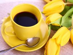 Yellow coffee cup and tulips which bring sunshine into my morning