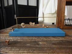 銘柄木の端材を使ってハンドメイドで仕上げたアンティーク風のかわいいピアススタンド細長タイプです小さいピアス(イヤリング)を6~8個ほど掛けられます土台にアクセサリーを置いて飾ることもできます土台は、トリトンブルーという褪せたブルーのようなカラーの水性ペイントで塗装しています(写真では、実際より鮮やかに写っています)真鍮ととてもよく合う色、アクセサリーを引き立てる色として選びましたマットな質感ですが、うっすらと木目が見える程度の一度塗りで仕上げています直径2mmの真鍮棒のラインが繊細でとてもおしゃれですお気に入りのピアス、イヤリングを自宅に飾ったり、アクセサリーを制作・販売している方は撮影やディスプレイに使って下さい端材で制作するピアススタンドは、それぞれサイズが異なりますので各々1点ものとなります☆ピアススタンドを3つ以上ご購入の場合は、ご注文前に送料をお問い合わせくださいませ☆商品保護のため、段ボールでの配送となります土台の木 約146×71×13mm真鍮棒 約2mm土台からのバーの高さ…