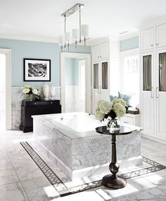 Abundant white cabinets and a stunning marble tub designed by Bob Williams of Mitchell Gold + Bob Williams via traditionalhome.com