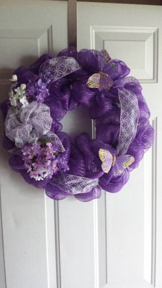 Butterfly wreath with Vibrant Purple deco mesh adorned with white flowers, white ribbon and a beautiful butterflies. Our wreaths are on a
