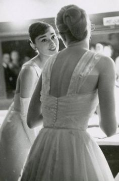 Audrey Hepburn and Grace Kelly backstage at the 28th Annual Academy Awards on March 21, 1956. Photographed by Allan Grant.