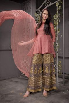 An eye catching, traditional silhouette with a hand embroidery stitched pattern is made to perfection to make every event a GRAND occasion. The peach organza short peplum shirt paired with block printing rust Indian raw silk bell bottom encapsulates Pakistani Fashion Casual, Pakistani Dresses Casual, Pakistani Dress Design, Indian Fashion, Kurta Designs, Kurti Designs Party Wear, Blouse Designs, Stylish Dresses For Girls, Stylish Dress Designs