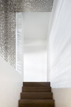 Modern wood staircase against metal artistic screen divide. Luxury modern duplex penthouse in Istanbul, Turkey designed by 1508 London. Project Esra. Designs featured on www.martynwhitedesigns.com