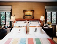 A striped throw and monogrammed linens on a bed.