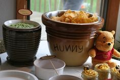 winnie the pooh birthday party using planting pots as honey pots to serve food in.