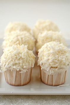Snowball Cupcakes... white cake, with white buttercream frosting, rolled in sweetened coconut, Mmmm...