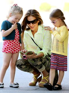 Mommy Sarah Jessica Parker, in shields, read a book to her adorable daughters mid-walk! Love their hot pink, girly sunnies!