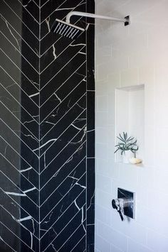 Glam bathroom a walk in shower boasting an accent wall clad in black marble herringbone tiles adjacent to a wall clad in white subway tiles fitted with a niche.
