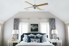 Beautiful bedroom features dove gray walls lined with a navy headboard, placed between two windows ...