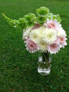 Crisantemos y campana Irlanda en florero cilíndrico de vidrio.