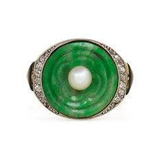 An Art Deco ring comprised of a carved jade panel set with a pearl in a diamond and black enamel mounting, in 18k white gold. Sasportas, France. CIrca 1925