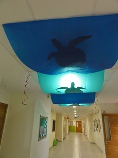 turtle cutouts of black bulletin board paper, placed in blue plastic table cloths hanged from the ceiling tiles with paperclips