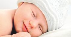 smiling european newborn baby in white hat