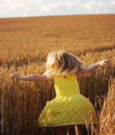 A little girl dancing in a field of wheat by Helen Rushbrook