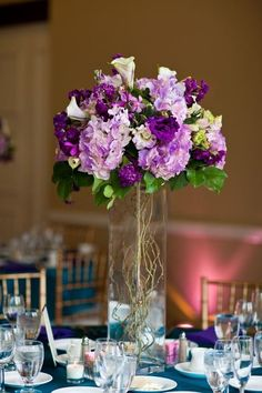 purple floral wedding reception tall wedding centerpiece / http://www.himisspuff.com/simple-elegant-all-white-wedding-color-ideas/12/