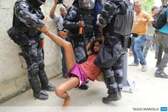 "BRAZIL, Rio de Janeiro : An activist is detained by riot police during a demonstration near the Museu do Indio (Indian Museum) ""Aldea Maracana"" (Maracana Village) in Rio de Janeiro, Brazil, on December 16, 2013. The demonstrators, among whom there were some 30 Amazonic natives, seized the museum protesting against its scheduled demolition to continue the works in the Mario Filho ""Maracana"" stadium ahead of the FIFA WC Brazil 2014. AFP PHOTO/TASSO MARCELO"