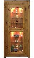 Curio cabinet DOOR w/interior light and glass shelves facing the hallway ...GREAT IDEA !....but wait...open the door and on the back side is a hidden gun safe.  www.hiddenpassages.com