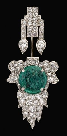 """An Art Deco platinum diamond and emerald jabot pin, Cartier. Petite round cut diamonds set into platinum """"flame"""" setting centring on a carved emerald cabochon. Signed Cartier, numbered."""