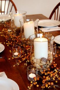 "table setting-Says Beth: ""Inspired by Pottery Barn, I filled the bottom of three glass hurricanes with mixed nuts and added pillar candles. I then arranged five small votive holders within orange-berried branches and called it done! Not only was it simple and elegant, but you could actually see the people sitting across the table from you."""