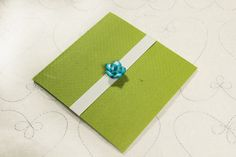 Square, lime green texture with little blue flower as a seal