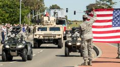 """Travis AFB Airmen and their families line Travis Blvd. as Brinlee Couts, 6, waves to the crowd during her Make-A-Wish Foundation """"send-off"""" parade April 4, 2016, at Travis Air Force Base, California."""