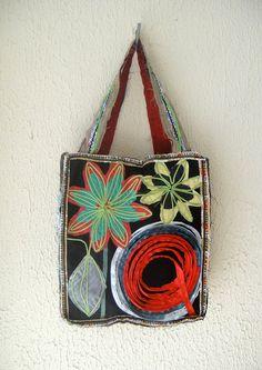 Bolsa tipo sacola (tote bag) com fitas e aplicação de tecidos.