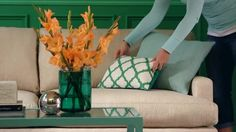 Pillows arranged prettily on a sofa add a flourish to living room. Bring a designer look to your sofa with these throw pillow arranging tips./