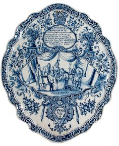 Blue Delft Plaque - 1735 - In scripted with a text referring Luke 2 versus 21, between two flower filled urns and four putty on the edges of a cartouche of flowers. Surrounding a central panel depicting the circumcision of Jesus Christ. A moulded self-frame with a foliate and scroll border. With two suspending holes - (height) 39.00 cm (width) 32.70 cm
