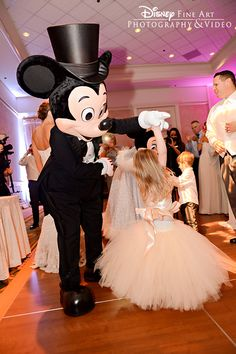 A little flower girl dances the night away with the Mouse himself at a Walt Disney World wedding reception