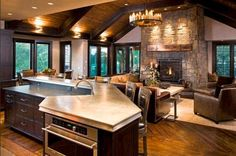 2 level island  open plan/kitchen/living, curved fireplace, wood paneled ceiling and beams, diagonal wide plank flooring  JohnKraemerSons