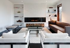 Modern minimalist living room with white built-ins shelves flanking modern floating fireplace with stacked tiles, white & gray Y rug, glass-top cocktail table, white modern chairs, gray chevron rug, brown sofa and x ottomans.