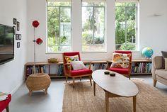 """המקום: מושב היוגב בעמק יזרעאל. ספרייה נמוכה בגוון עץ, שמורכבת משלוש יחידות (""""איקאה""""), מוקמה לאורך הקיר, ומעליה שלושה חלונות. לפניה הוצבו שתי כורסאות ישנות שרופדו באדום. שולחן קפה אובאלי בסגנון שנות ה-50 משלים את פינת הישיבה."""