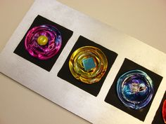 Upcycle art project using the bottom of soda cans and alcohol ink.