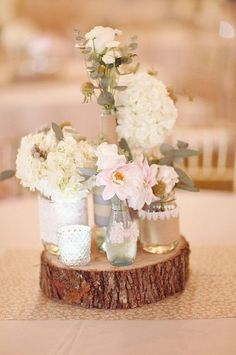 Tree stump centerpiece with assorted jars and white flowers