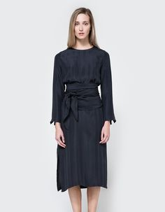 Modern dress from Rodebjer in Anthracite. Crew neckline. Back button-and-loop closure. Long sleeves with slit detailing. Removable wide belt. Side slits. Straight silhouette. Casual fit. Unlined. • Charmeuse • 100% silk • Dry clean
