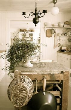 FARMHOUSE – INTERIOR – early american decor inside this vintage farmhouse seems perfect with shelves, baskets, pans on island, and egg carrier.