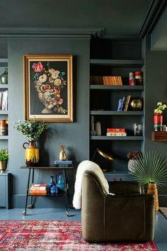 decoración en colores oscuros, colores para salones, salon pequeño, paredes azul oscuro grisáceo, cuadro con flores, sillon de pile, alfombra roja, estantería con libros