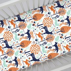 "Crib Fitted Sheet in and Navy and Orange Woodland Animals by Carousel Designs.  Our fitted crib sheets feature deep pockets and have elastic all the way around the edges to hug mattresses securely. Fits standard crib mattresses, measuring approximately 28"" x 52""."