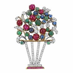 Platinum, Gold, Diamond, Cabochon Colored Stone and Ruby Bouquet Brooch   The bouquet embellished by 28 round cabochon rubies, sapphires and emeralds, accented by 6 collet-set old-mine cut diamonds, atop a stylized vase of diamond-set bands, set throughout with small old-mine, cushion and rose-cut diamonds, the base edged by square-cut rubies, circa 1935, approximately 12.7 dwts.
