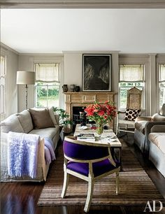 A painting by Beverly Pepper overlooks the living room, which features a sofa, cocktail table, and floor lamp from Lucca Antiques | archdigest.com