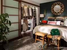 Photo by the Stow Company, Design by Storybook Interiors of Grand Rapids, Michigan. Master bedroom, dark green wall, closet organization, bedding
