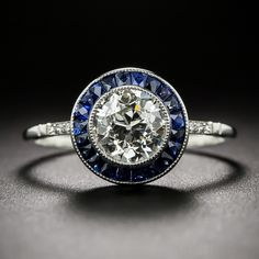 A central European-cut diamond, weighing just a smidgin shy of one-and-a-quarter carat, sparkles mightily from the center of a rich royal-blue halo of scissor-cut calibre sapphires. The carat diamond is of vintage; the platinum ring was recentl Halo Engagement Rings, Designer Engagement Rings, Halo Rings, Vintage Engagement Rings, Vintage Rings, Estilo Art Deco, Antique Diamond Rings, European Cut Diamonds, Round Diamonds