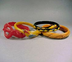 Group of Four Bakelite and Celluloid Bracelets  Each with snake decoration, two encrusted with rhinestones. Widest 5/8 inch.    Sold for 1,000 (Includes Buyer's Premium)