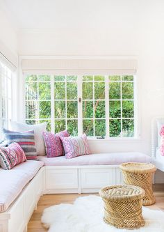 Bright corner nook with vintage textiles and bench seating.
