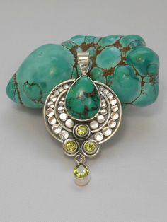 "Handmade teardrop Artisan Tibetan Turquoise center gemstone is adorned with 4 faceted Peridot gemstones including 1 teardrop dangle, bezel-set in 925-hallmarked sterling silver. Length: 2"" including bail. Width: 1.2"""