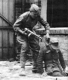Russian armed with PPSh-41 machine pistol plucks German soldier out of a sewer during the vicious fight for Berlin, April 1945.